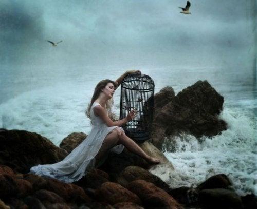 Mujer abriendo una jaula de pájaros.