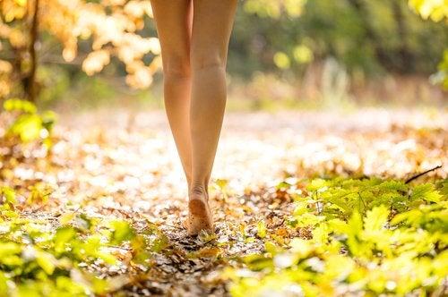 Woman walking barefoot in a wood.