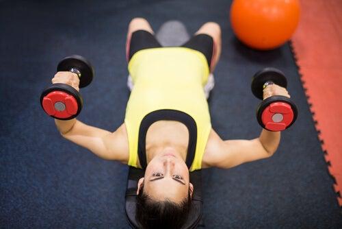 Mujer realizando levantamiento de pesas recostada
