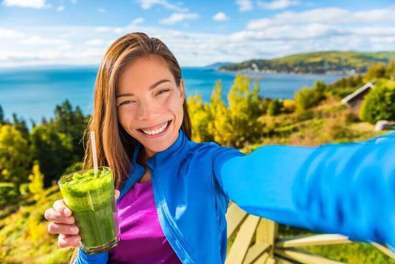 Chica sonriendo con un batido verde.