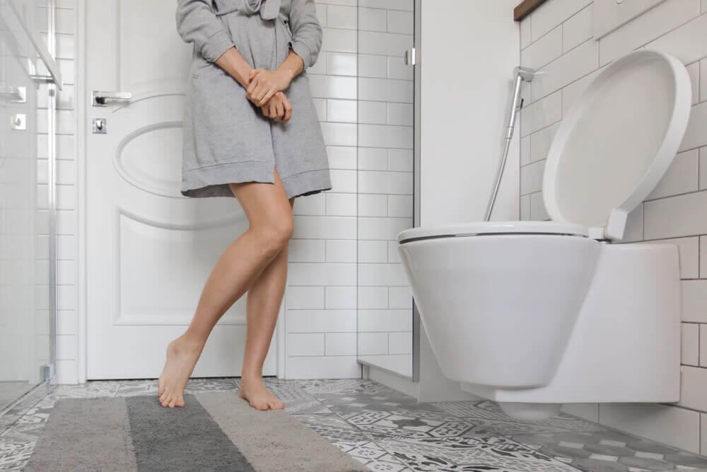Mujer en el baño con vejiga hiperactiva.