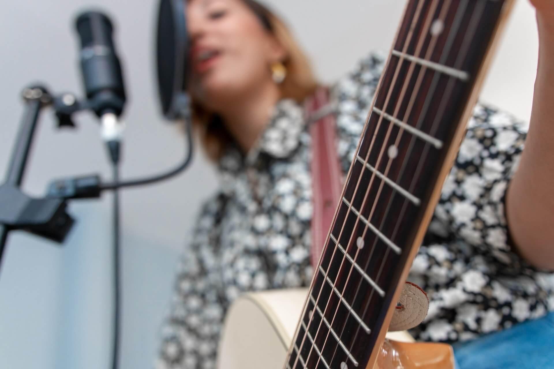 Mujer cantando y tocando guitarra