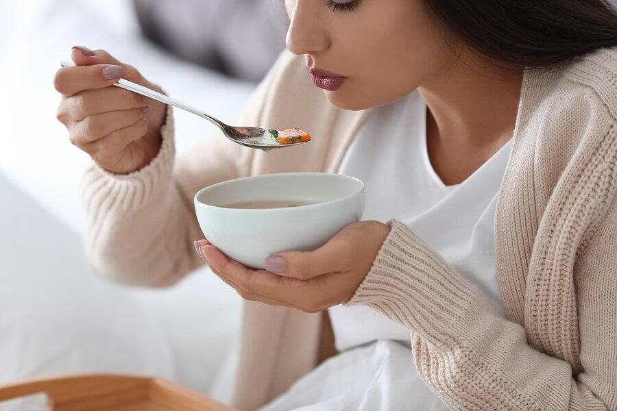Mujer comiendo cuenco de sopa.