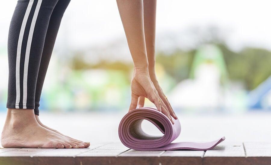 Mujer desplegando esterilla de yoga