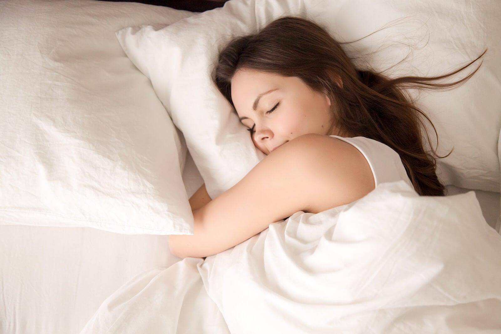 Mujer durmiendo de lado abrazada a la almohada