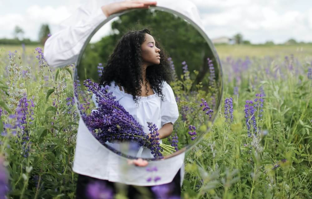Mujer sujetando un espejo en un campo de lavanda.