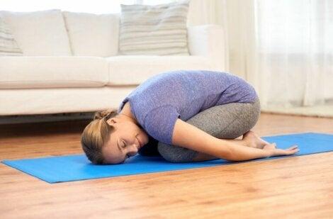 Mujer realizando la postura del niño en sesión de yoga.