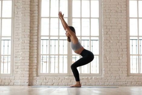 Mujer haciendo la postura de la silla en clase de yoga.