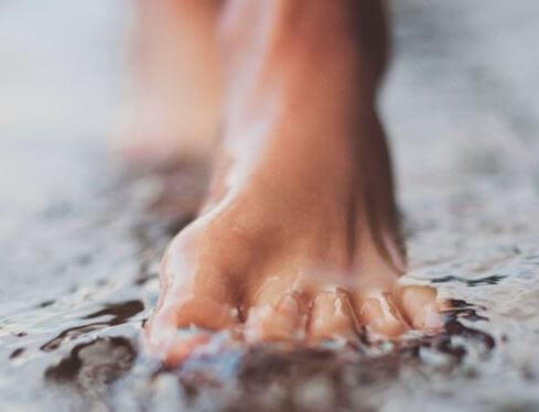 Pies caminando sobre suelo mojado
