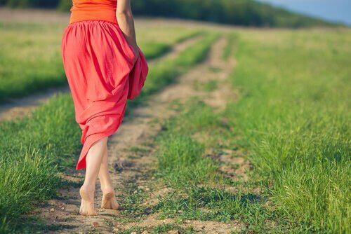 Mujer-con-falda-roja-andando-por-un-camino