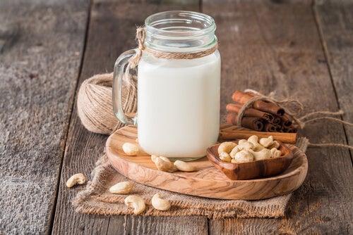 Bote con leche, frutos secos y ramas de canela.