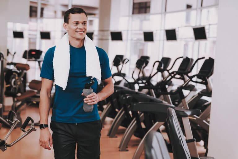 Chico en el gimnasio sosteniendo botella de agua.