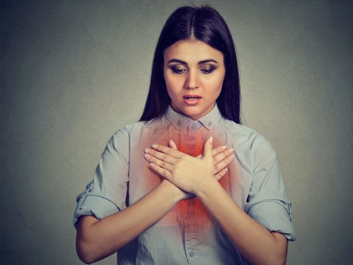 Mujer con las manos en el pecho donde hay un dibujo de sus vías respiratorias.