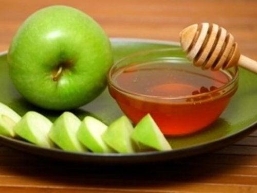 Grønne epleskiver og en bolle med honning