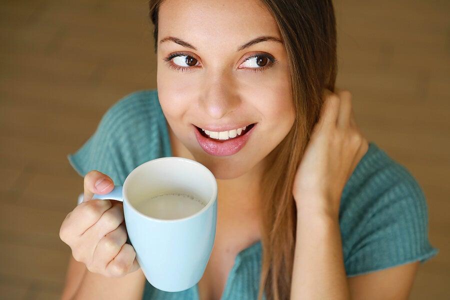 Mujer bebiendo leche en una taza.