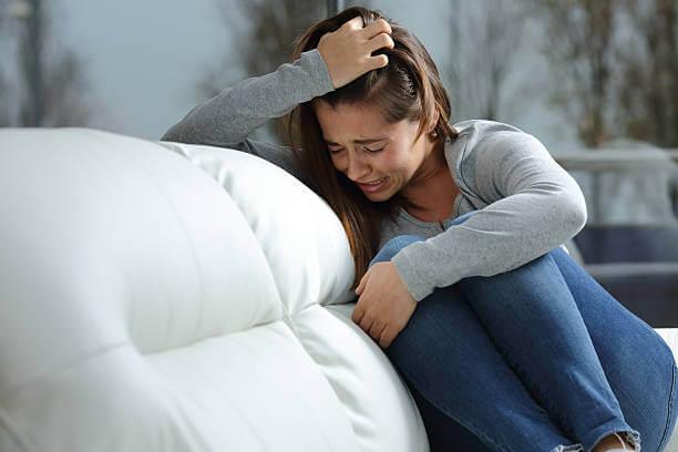 Mujer lamentándose en el sofá