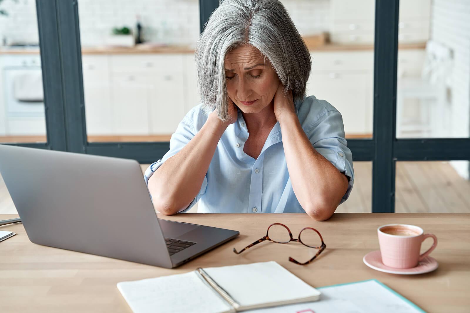 Mujer con dolor de cuello por mala postura frente al ordenador.