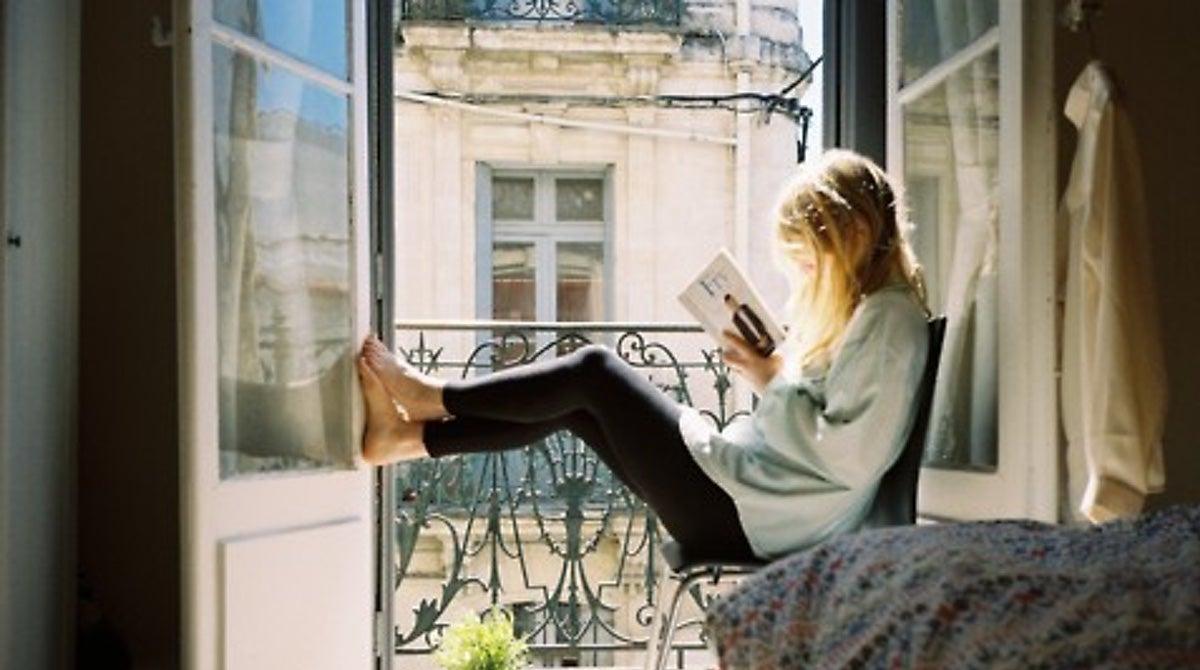 Mujer leyendo en la ventana.