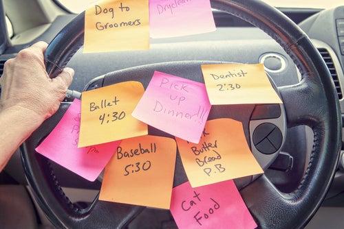 Persona en el coche con el volante lleno de notas escritas con las cosas pendientes de hacer