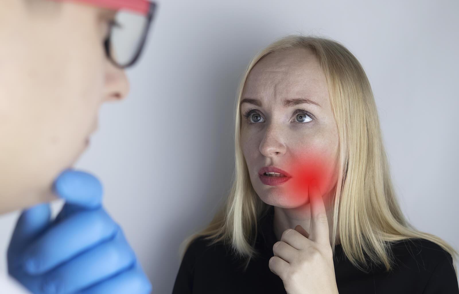 Médico y paciente averiguando causas del dolor mandibular.