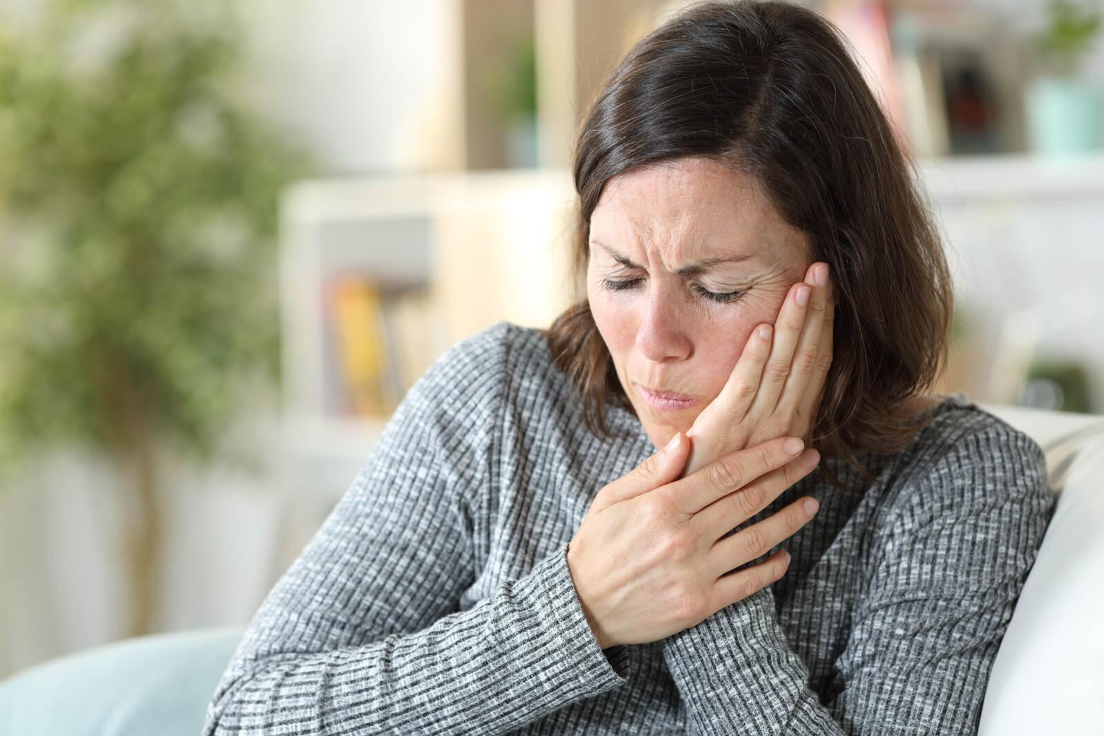 Mujer sentada con dolor mandibular.