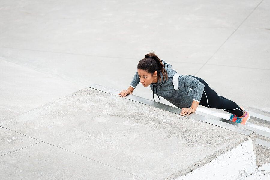 Mujer haciendo flexiones en las escaleras.