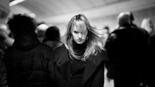 Mujer pensativa entre otras personas