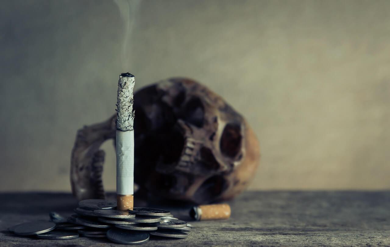 Cigarrillo, calavera y monedas.