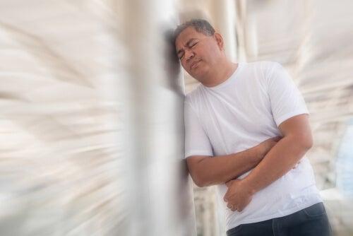 Hombre con gases apoyado en una pared.