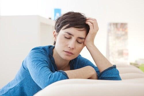 Mujer apoyada sobre su brazo con cansancio.