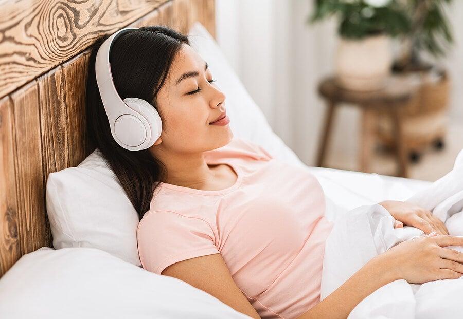 Mujer con cascos escuchando música relajante en su cama.
