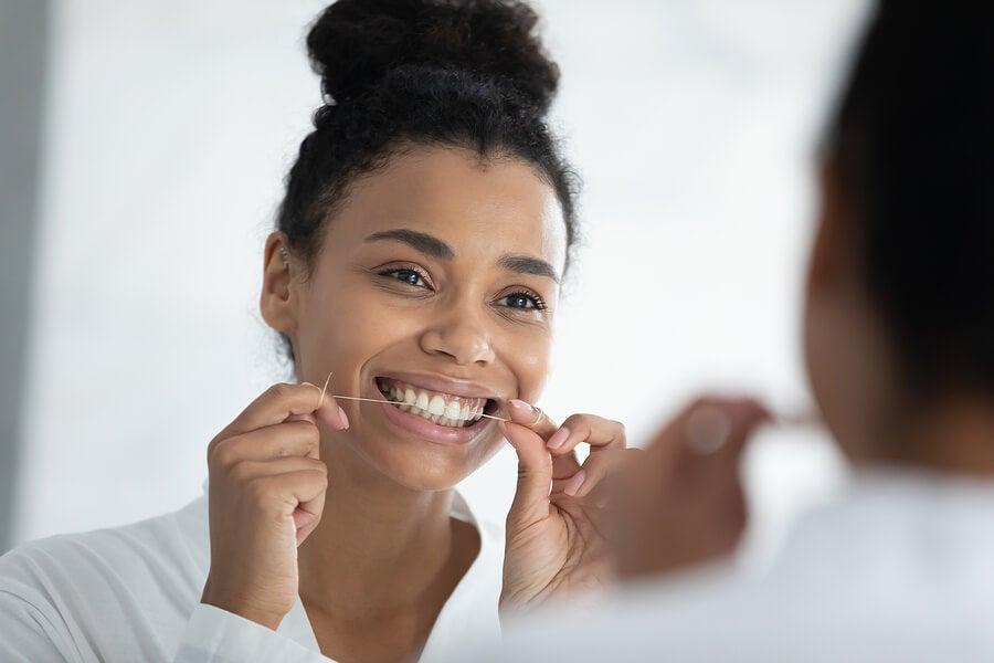 Mujer usando hilo dental