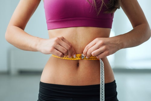 Mujer midiéndose con una cinta métrica el contorno del abdomen después de seguir una dieta cetogénica