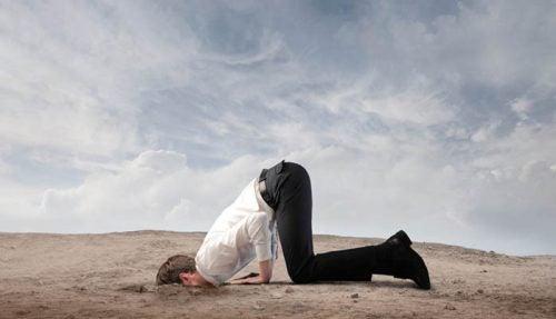 hombre con la cabeza en la tierra escondiendo sus emociones