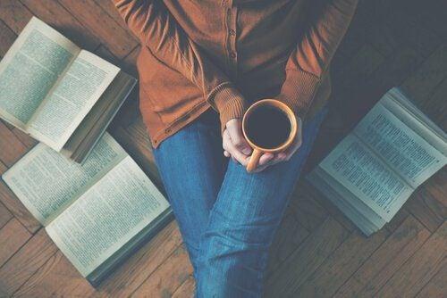 Mujer-tomando-café-sentada-en-el-suelo-con-libros