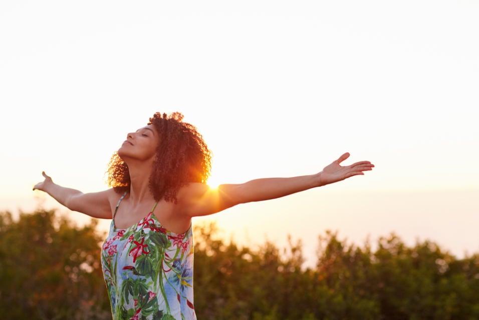 Mujer joven con los brazos abiertos toma aire dándose un respiro y romper con la rutina.
