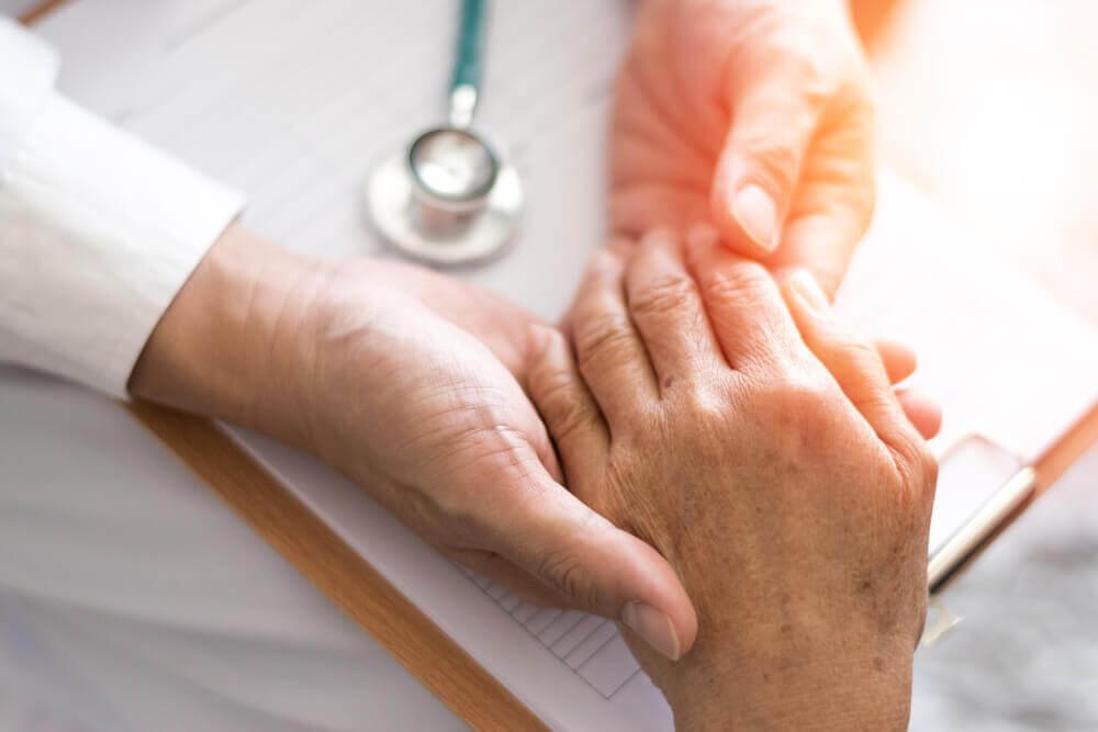 Médico sujetando mano de paciente con artritis.