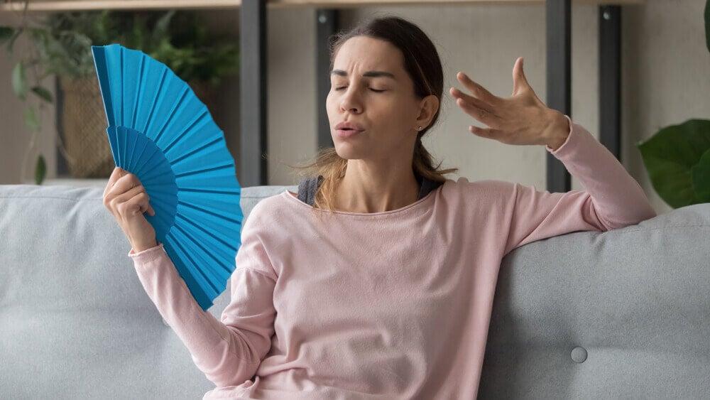 Mujer abanicándose por calor.