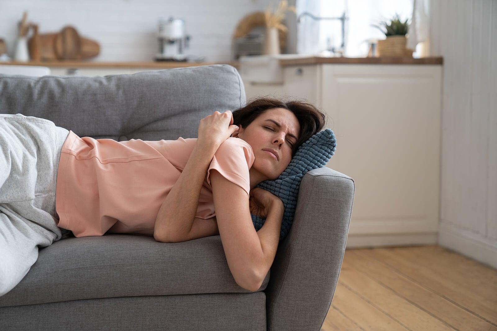 Mujer en el sofá con agotamiento extremo.