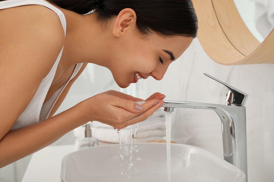 Mujer lavándose el rostro en el lavamanos