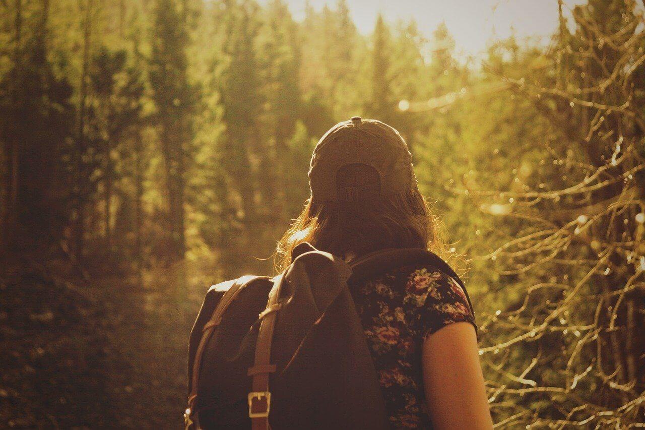 Mujer con mochila en el bosque.