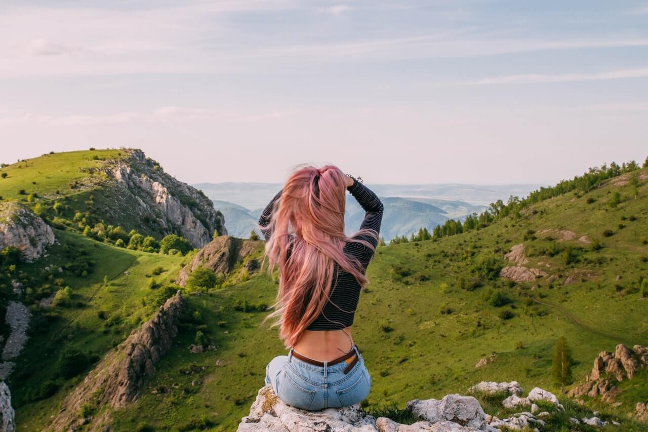 Mujer en las montañas mirando el paisaje.