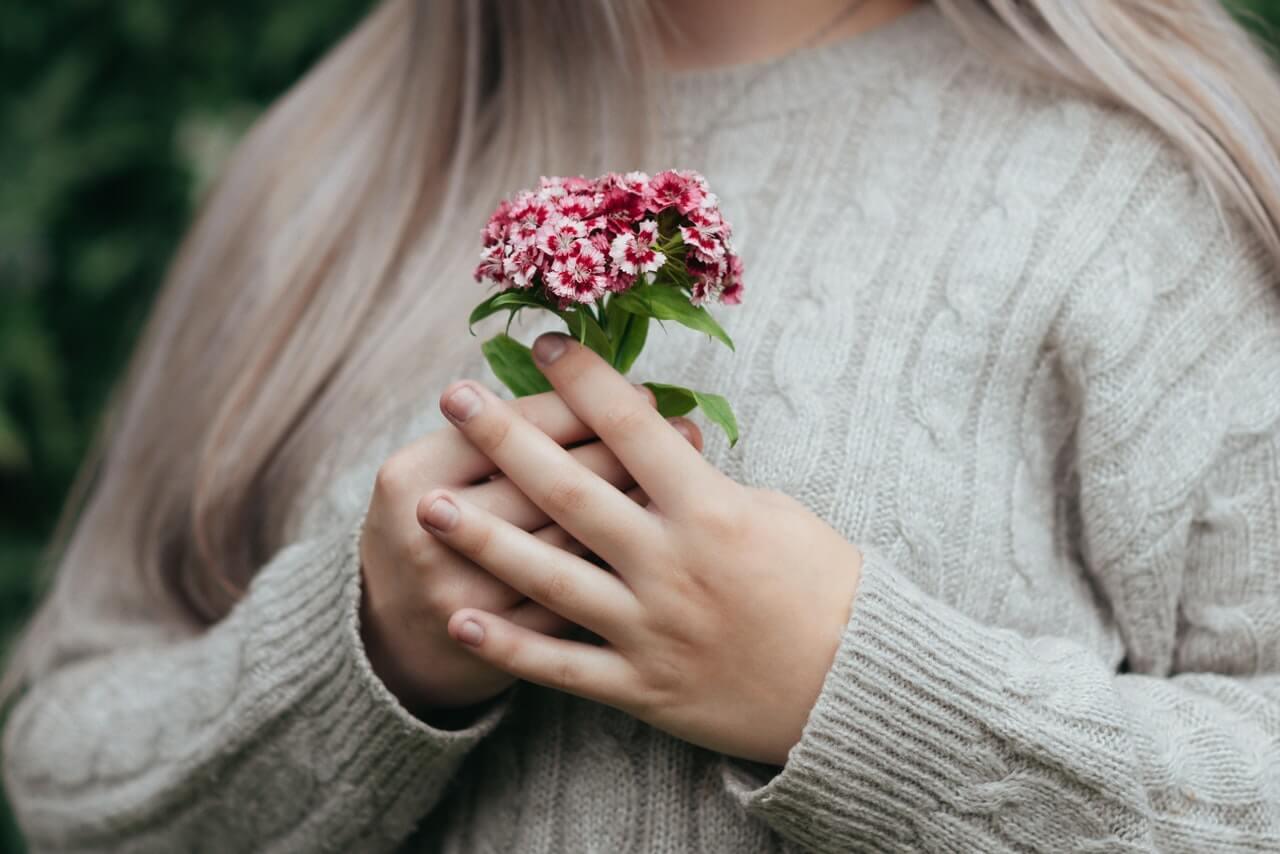 Mujer sujetando un ramito de florecillas.