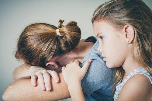 Niña abrazando a su madre con depresión