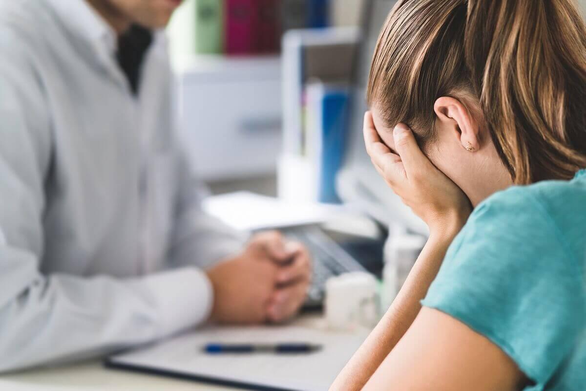 Paciente llorando en consulta con su médico.