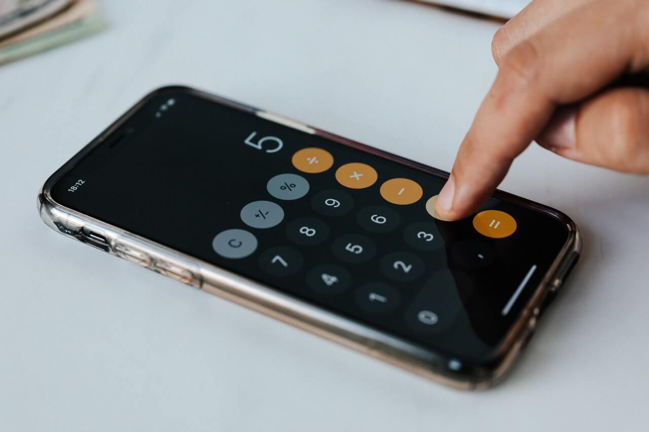 Persona usando calculadora en el teléfono.
