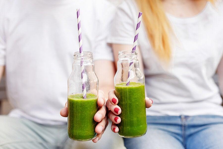 Personas con botellas de batidos verdes.