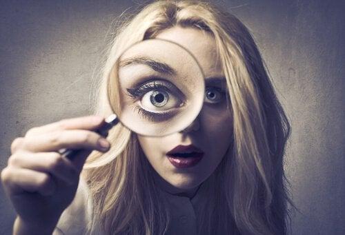 Mujer observando a través de una lupa por puro perfeccionismo