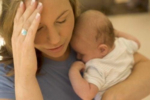 Madre preocupada con su bebé en brazos
