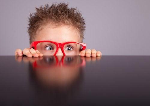 Niño pequeño con gafas rojas a quien le llama la atención lo nuevo